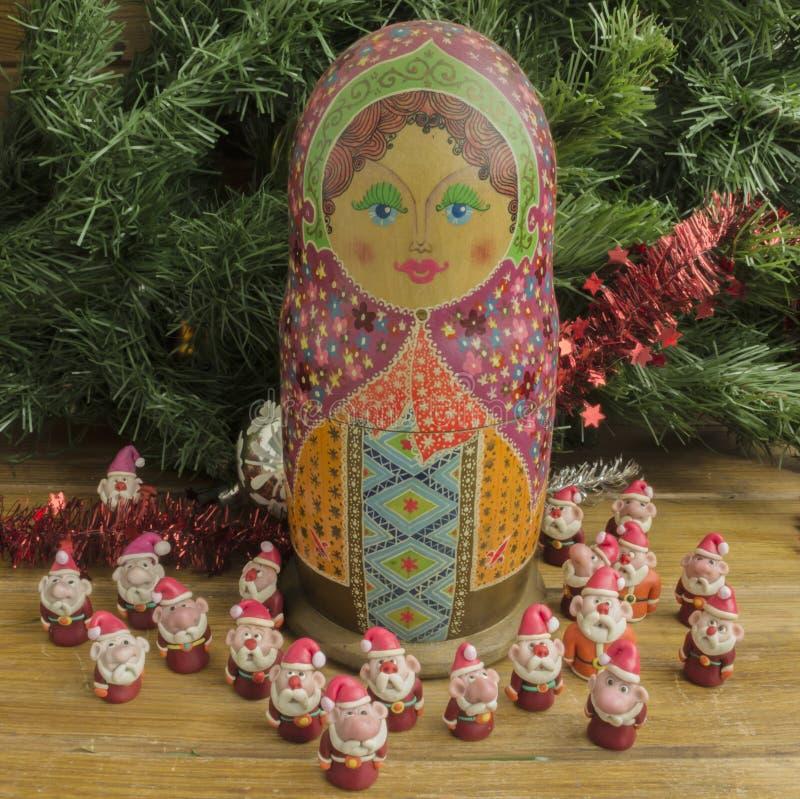 Painted wooden matrioshka doll and Santa Clauses from modeling clay. Santa Clauses around matrioszka doll stock photos