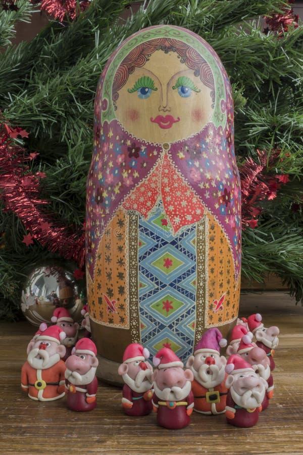 Painted wooden matrioshka doll and Santa Clauses from modeling clay. Santa Clauses around matrioszka doll royalty free stock photos