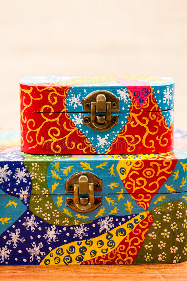 Painted, wooden small boxes for multiple purposes and jewels. On a wooden surface royalty free stock images