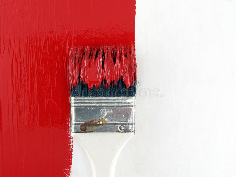 close-up paint brush painting red color on white wooden wall, renovate and decorate old house stock image