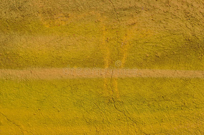 Painted yelllow texture. Rough cracked plastered wall airbrushed in yellow hues stock photos