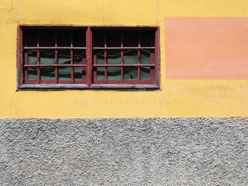 Painted yellow and h narrow red framed window. Old painted yellow and grey concrete wall with narrow red framed window with bars and distressed cracked texture royalty free stock image