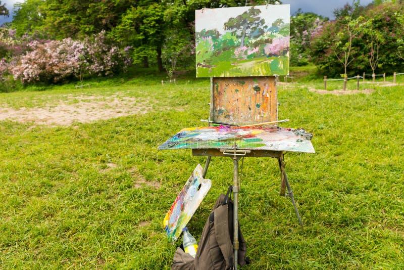 Painter& x27; 在三脚架的s写生簿在庭院里 免版税库存图片