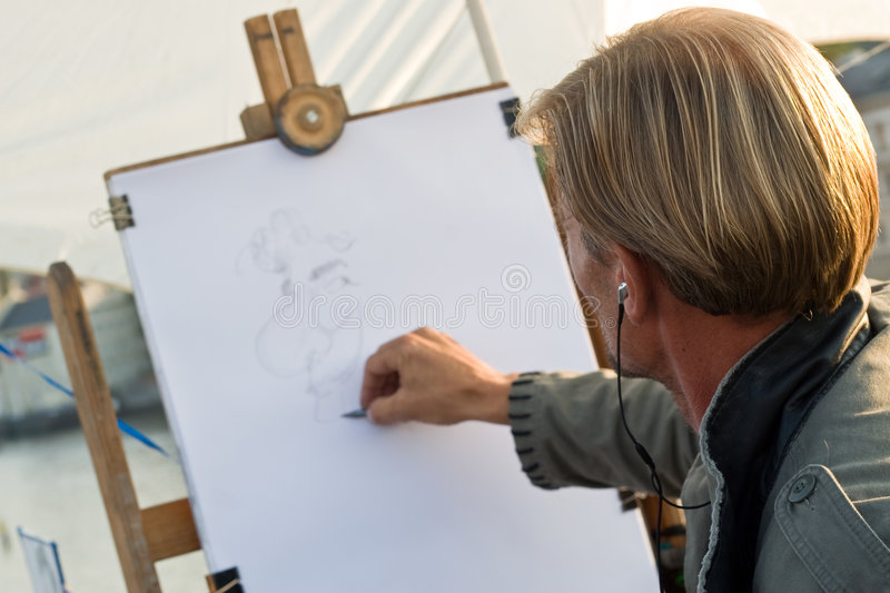 Painter. Street artist at work painting a portrait royalty free stock photography