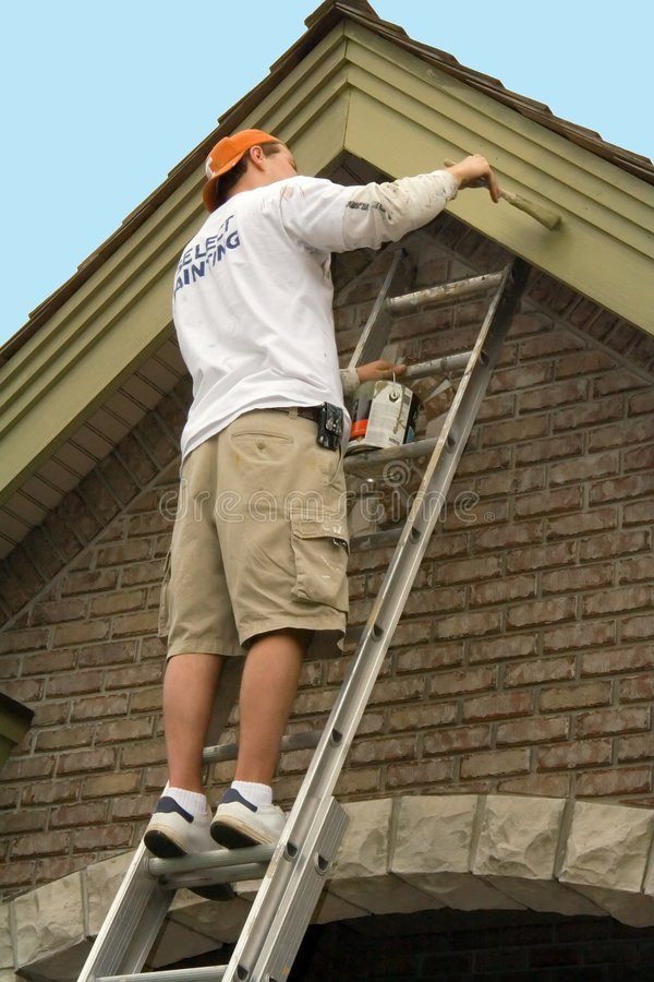 Painter. On a ladder, painting a house exterior