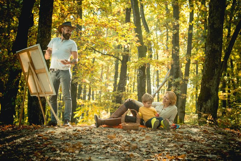 Painter artist with family relaxing in forest. Painting in nature. Start new picture. Capture moment. Beauty of nature stock photo