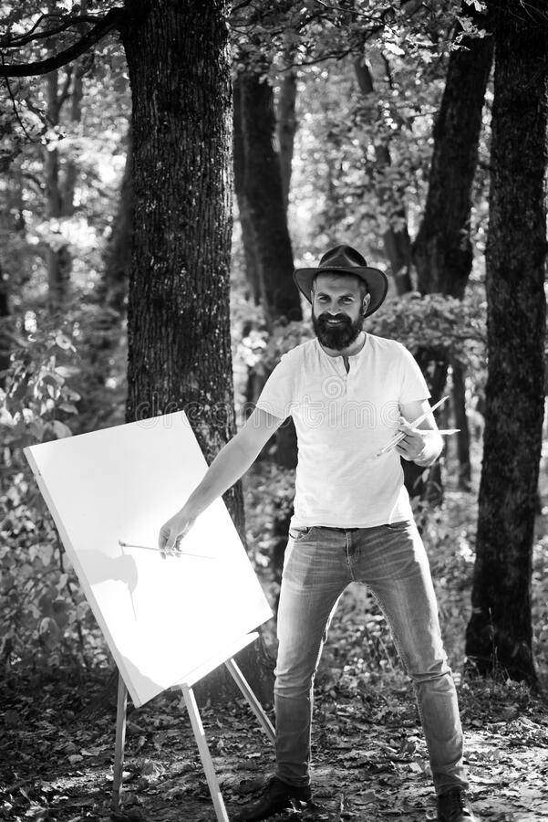 Painter artist forest. Art concept. Painting in nature. Start new picture. Painter with easel and canvas. Capture moment. Bearded man painter looking for royalty free stock photography