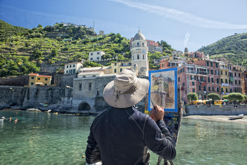 Painter Artist in Vernazza while painting a church stock images