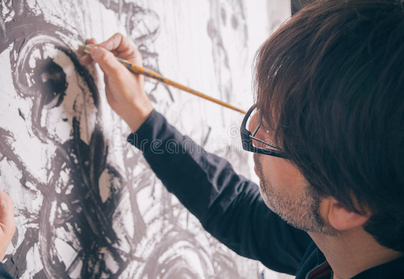 Painter artist working in modern oil canvas. Closeup of painter artist working in a modern abstract oil canvas in his studio royalty free stock photos