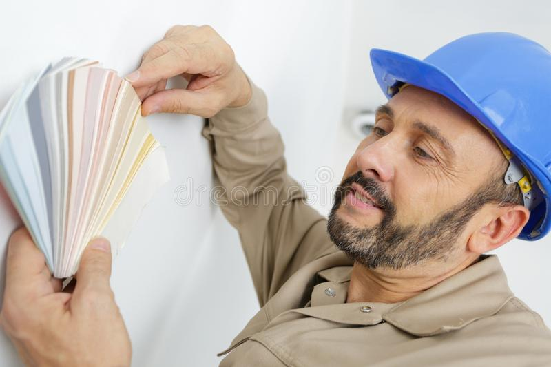Painter in blue hat holding color swatches royalty free stock photos
