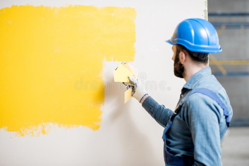 Painter comparing colors. Painter in blue workwear comparing yellow painted wall with color swatches indoors royalty free stock image