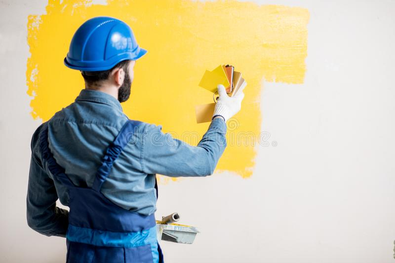 Painter comparing colors. Painter in blue workwear comparing yellow painted wall with color swatches indoors royalty free stock photography