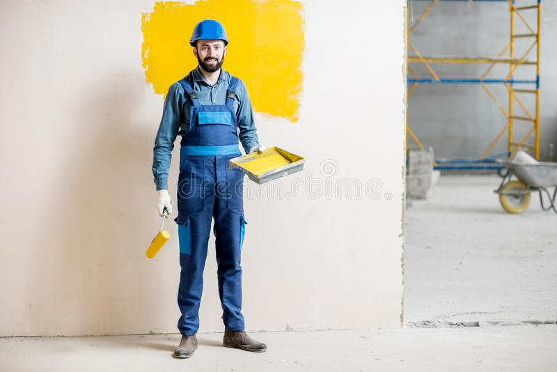 Painter at the construction site. Full body portrait of a painter in working uniform standing with paint roll at the construction site royalty free stock photo