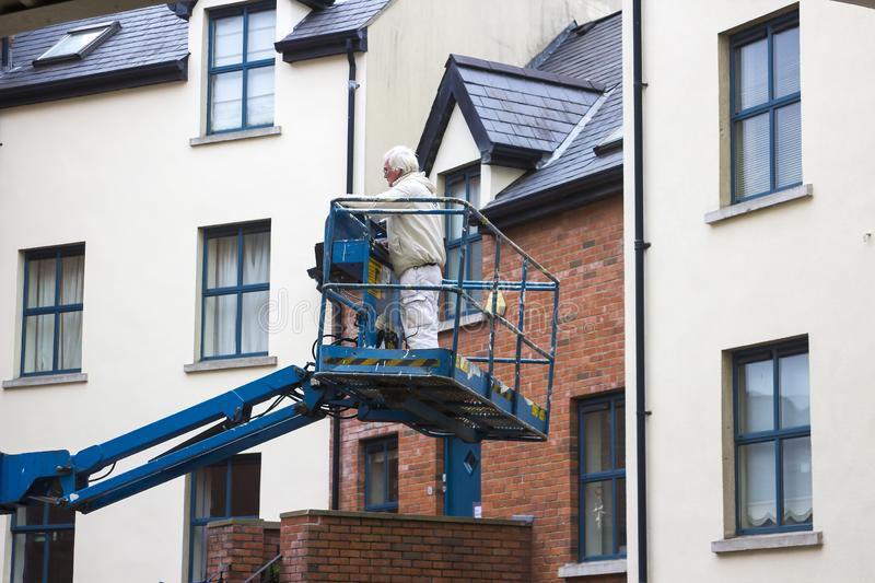 A Painter and Decorator being raised in a Cherry Picker crane royalty free stock photo