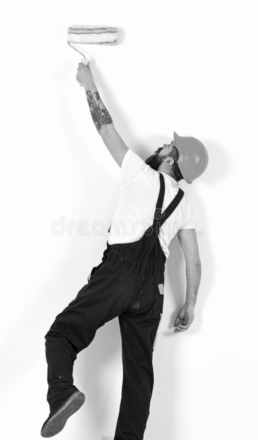 Painter, decorator, construction worker works in front of white wall, holds paint roller, white background. Man in royalty free stock photos