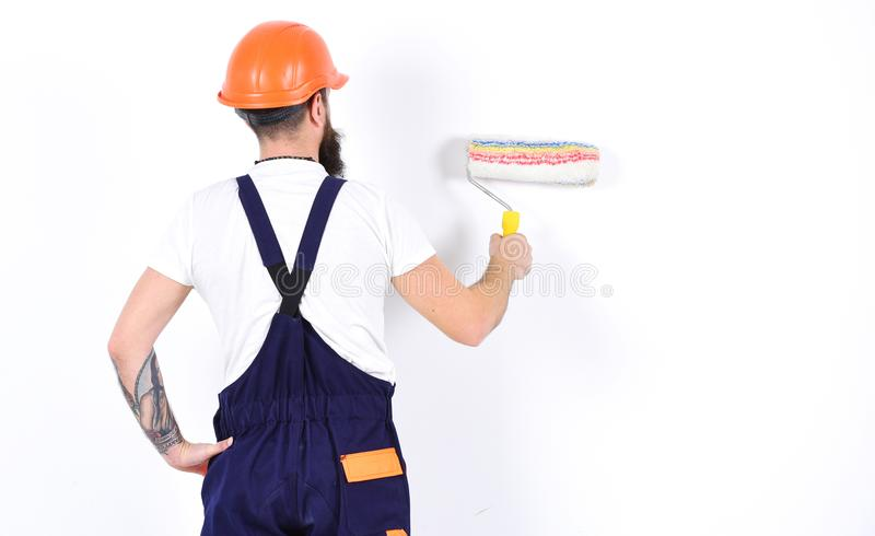 Painter, decorator, construction worker works in front of white wall, holds paint roller, white background. Renovation stock photography