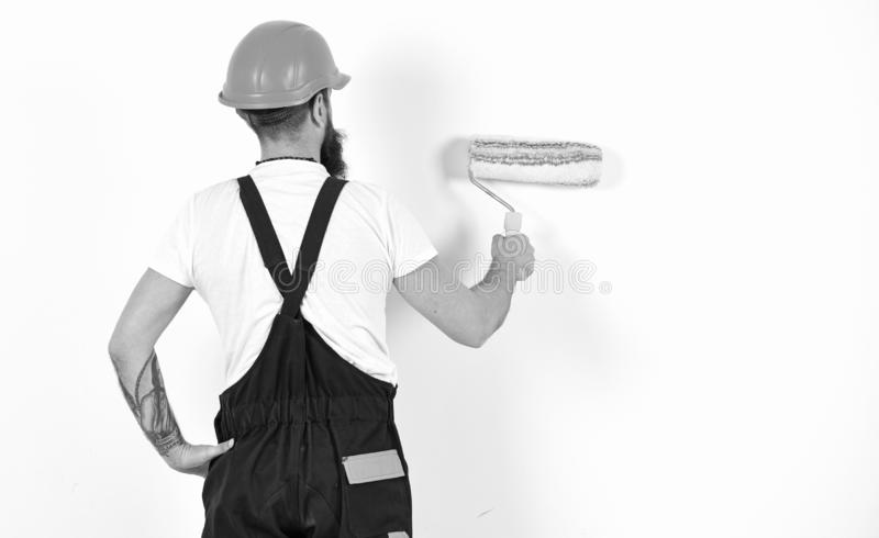 Painter, decorator, construction worker works in front of white wall, holds paint roller, white background. Renovation stock photos