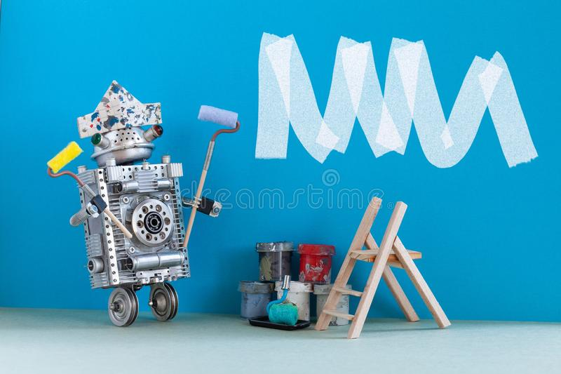 Painter decorator at work. Robot designer with paint roller and buckets. Interior room redecoration concept. Copy space. royalty free stock photos