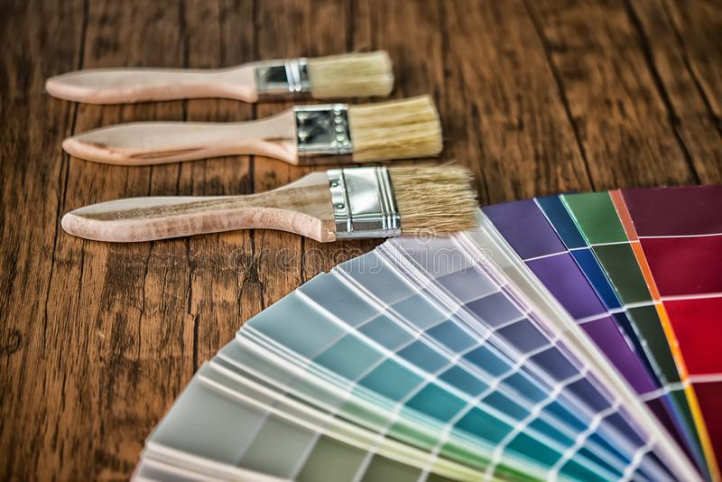 Painter and decorator work table with house project, color swatches, painting roller and paint brushes stock photos