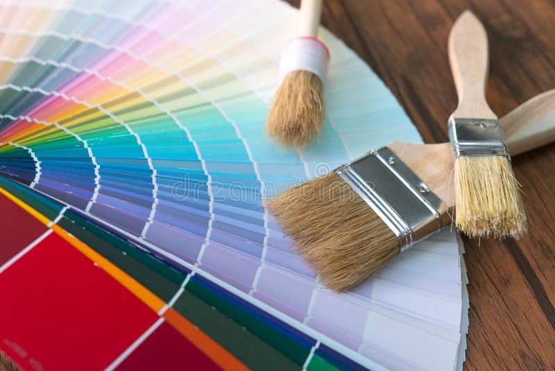 Painter and decorator work table with house project, color swatches, painting roller and paint brushes stock images