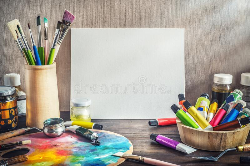 Painter equipment in a artist studio: empty canvas, tube of oil stock photography