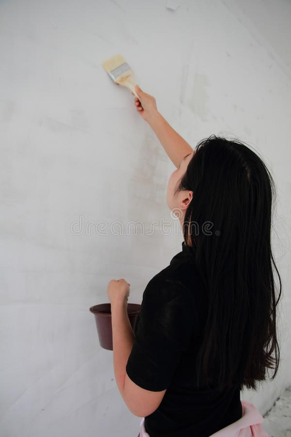 Painter Painting a House Wall with a Paint Roller. Painter hand holding a fabric roller and painting a house wall with satin finish white latex paint stock photos