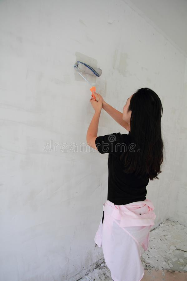 Painter Painting a House Wall with a Paint Roller. Painter hand holding a fabric roller and painting a house wall with satin finish white latex paint royalty free stock image