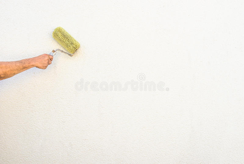 Painter hand is painting a house wall with roller. stock photos