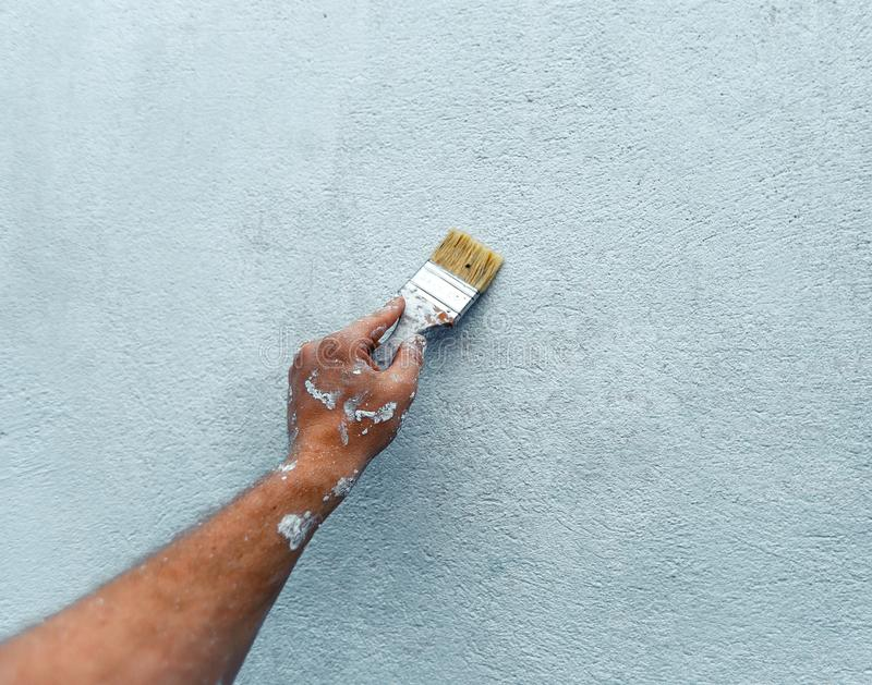Painter Hand Paints The Wall With Paint, Close-up With Copy-Space. Home Renovation Concept stock photo