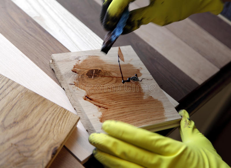 Painter holding a paintbrush over wooden surface stock image