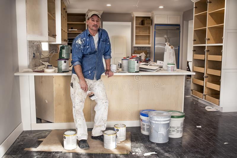 Painter holding wet paint brush standing in messy remodeled home kitchen surrounded by paint cans royalty free stock photos