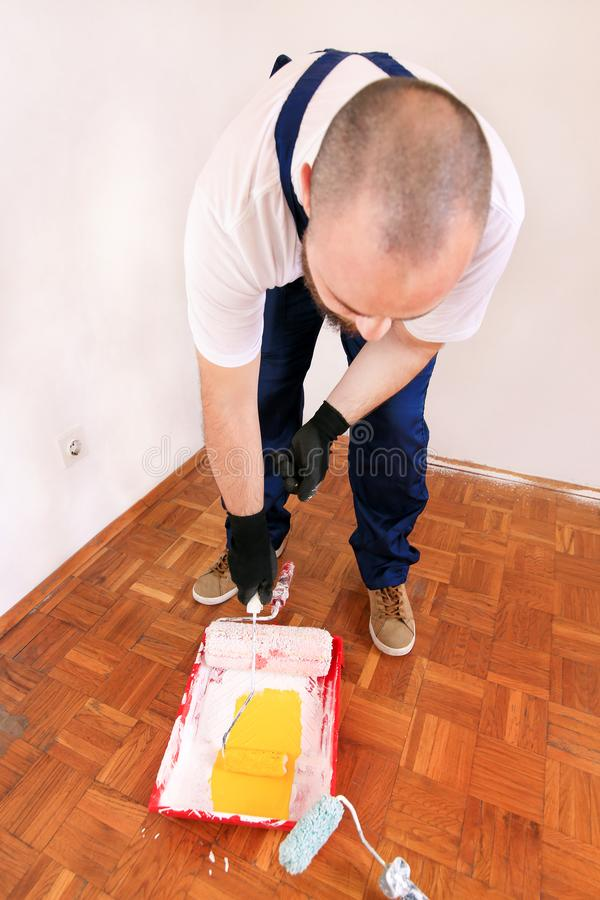 Painter holds roller brush paint in hand and mixes yellow paint in container and red bowl for color mixing. stock images