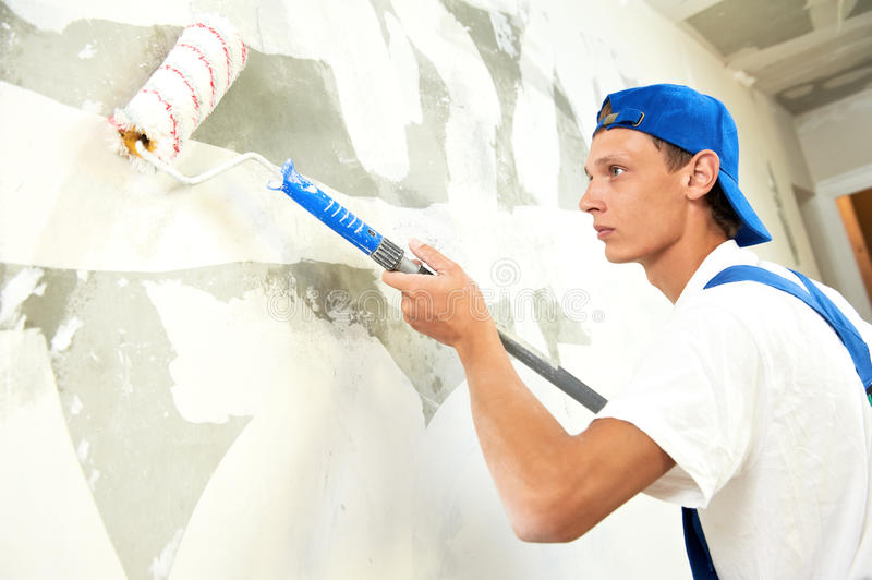 Painter at home renovation work with prime. One painter with paint roller making wall prime coating at home repair renovation work stock photo