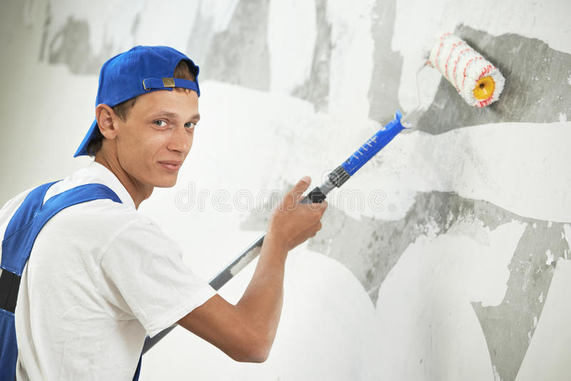 Painter at home renovation work with prime. One painter with paint roller making wall prime coating at home repair renovation work royalty free stock photography