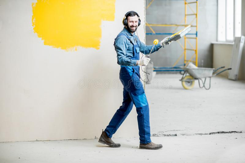 Painter listening to the music during the work. Happy repairman listening to the music with headphones during the painting wall indoors royalty free stock photography