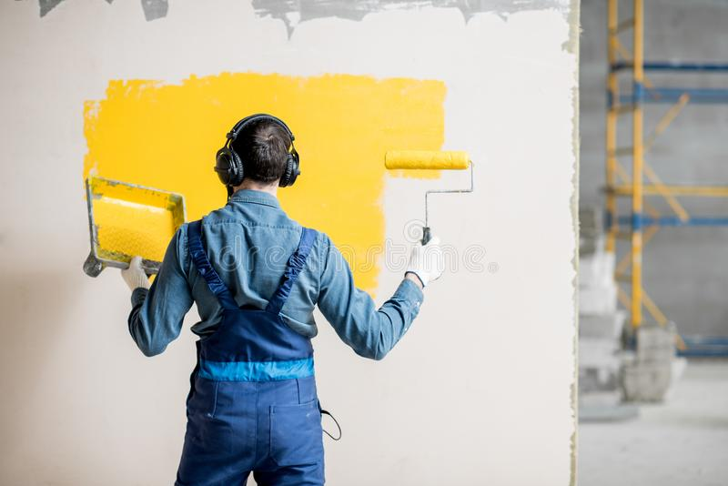 Painter listening to the music during the work. Happy repairman listening to the music with headphones during the painting wall indoors royalty free stock photos