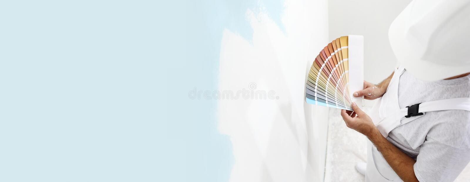 Painter man with color swatches in your hand, choice of colors concept, on big blank wall for copy space and web banner. Background stock image