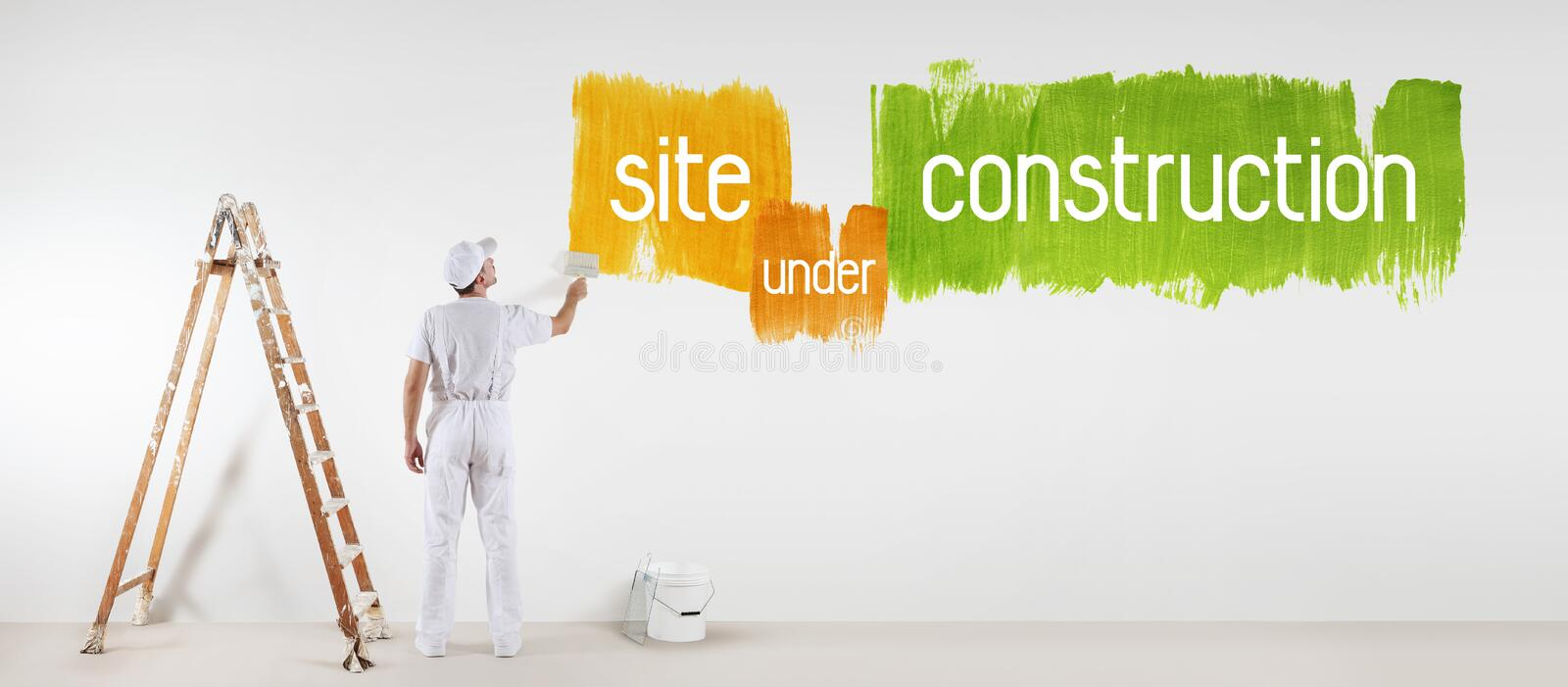 Painter man with paint brush drawing under construction text stock photo