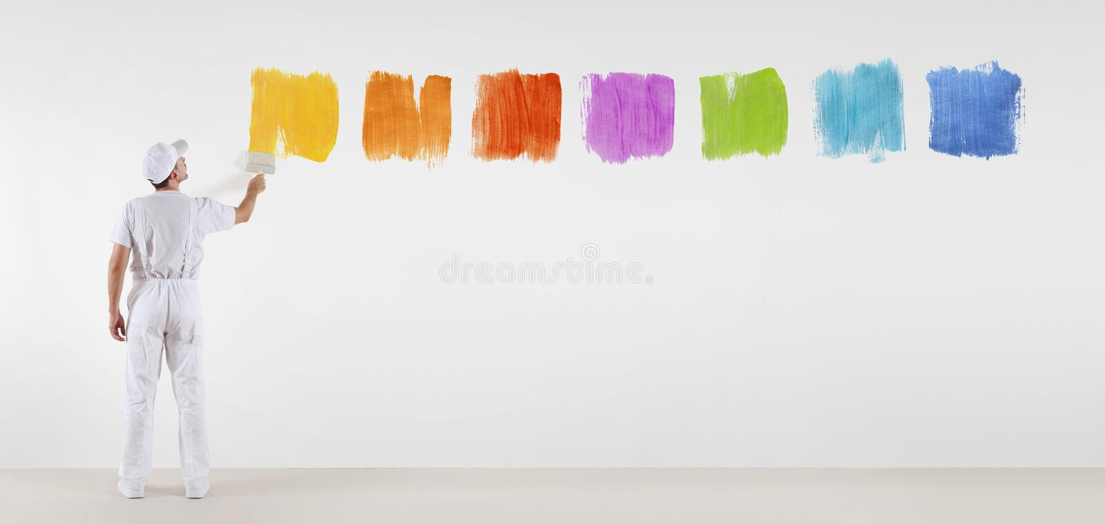 Painter man with paint brush painting color samples isolated. On blank white wall background, web banner menu stock photo