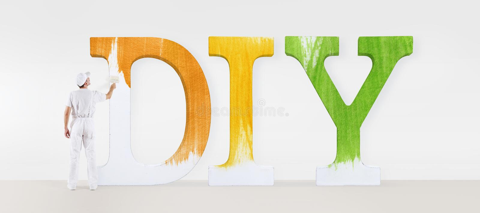 Painter man with paint brush, painting a text diy on white blank royalty free stock photo