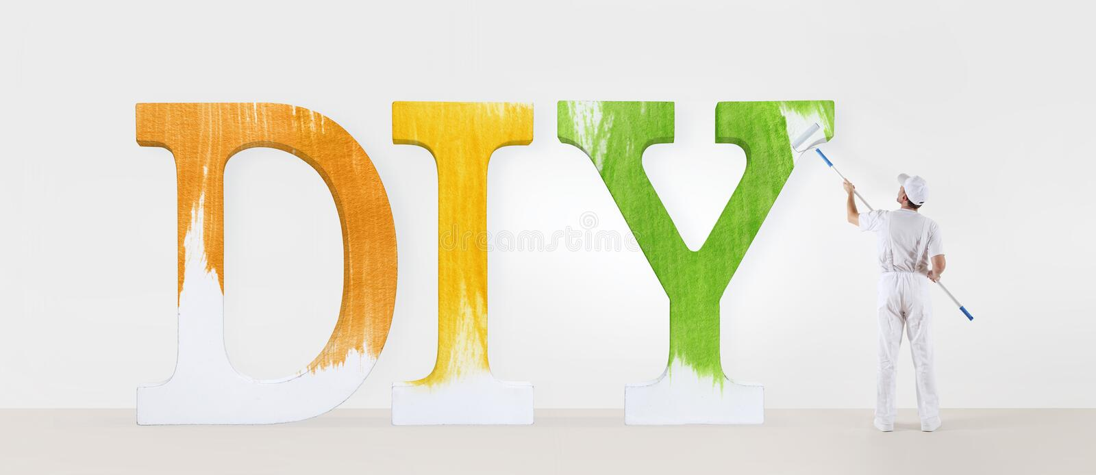 painter man with paint roller, painting a text diy on white blank wall, background house service concept. stock images