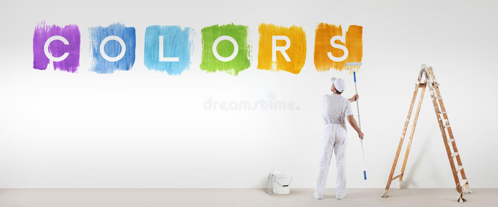 Painter man painting colors text isolated on blank white wall. Background, banner web royalty free stock photos