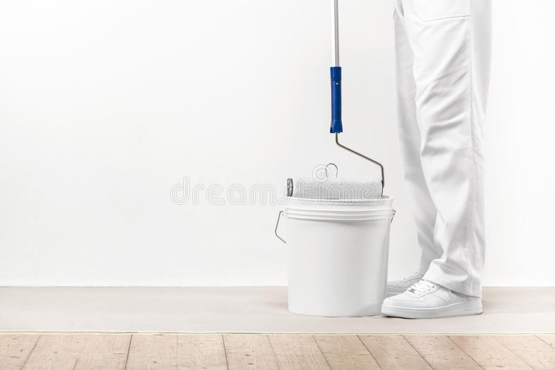 Painter man takes the color with paint roller from the bucket. royalty free stock photo