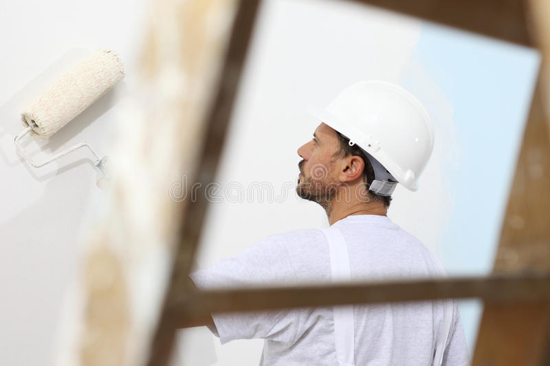 Painter man at work with a paint roller, wall painting stock image