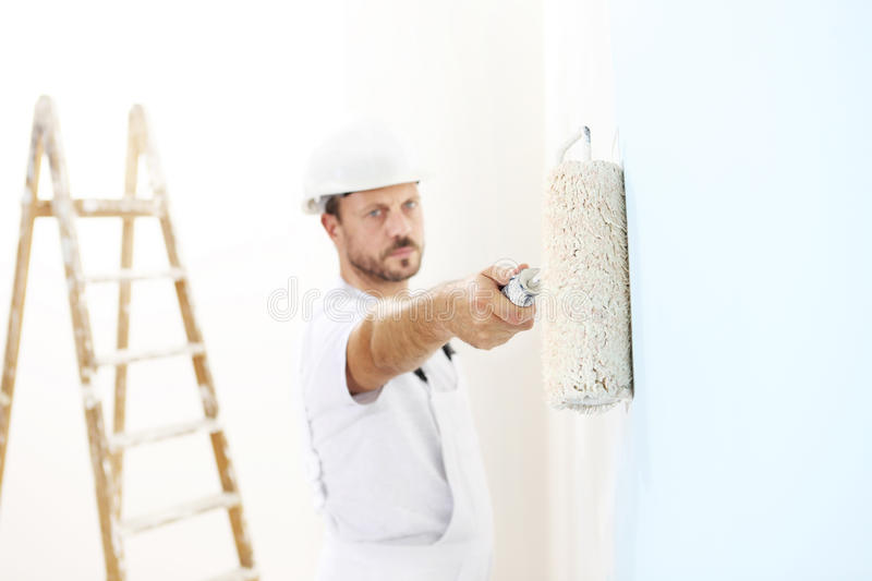 Painter man at work with a paint roller, wall painting. Concept stock photos