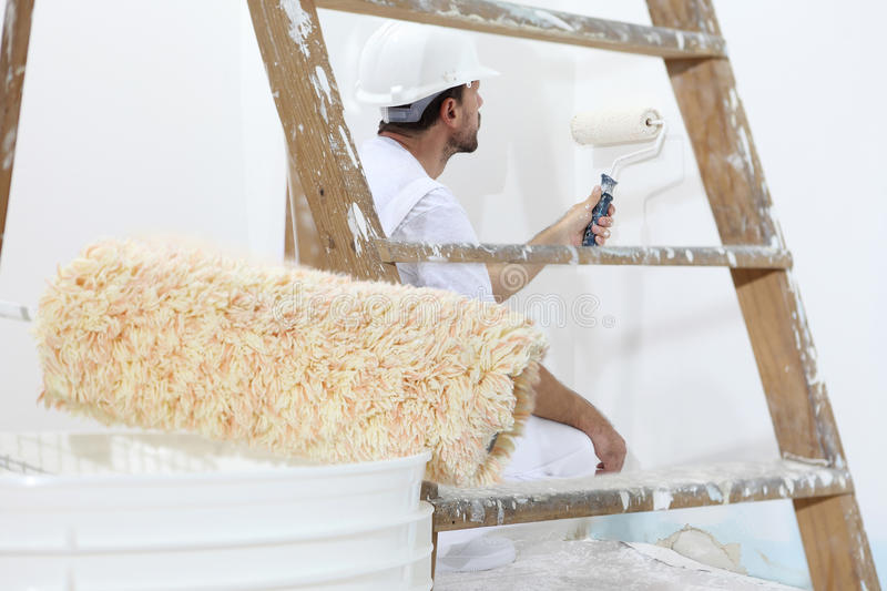 Painter man at work with paint roller, wall painting concept stock photos