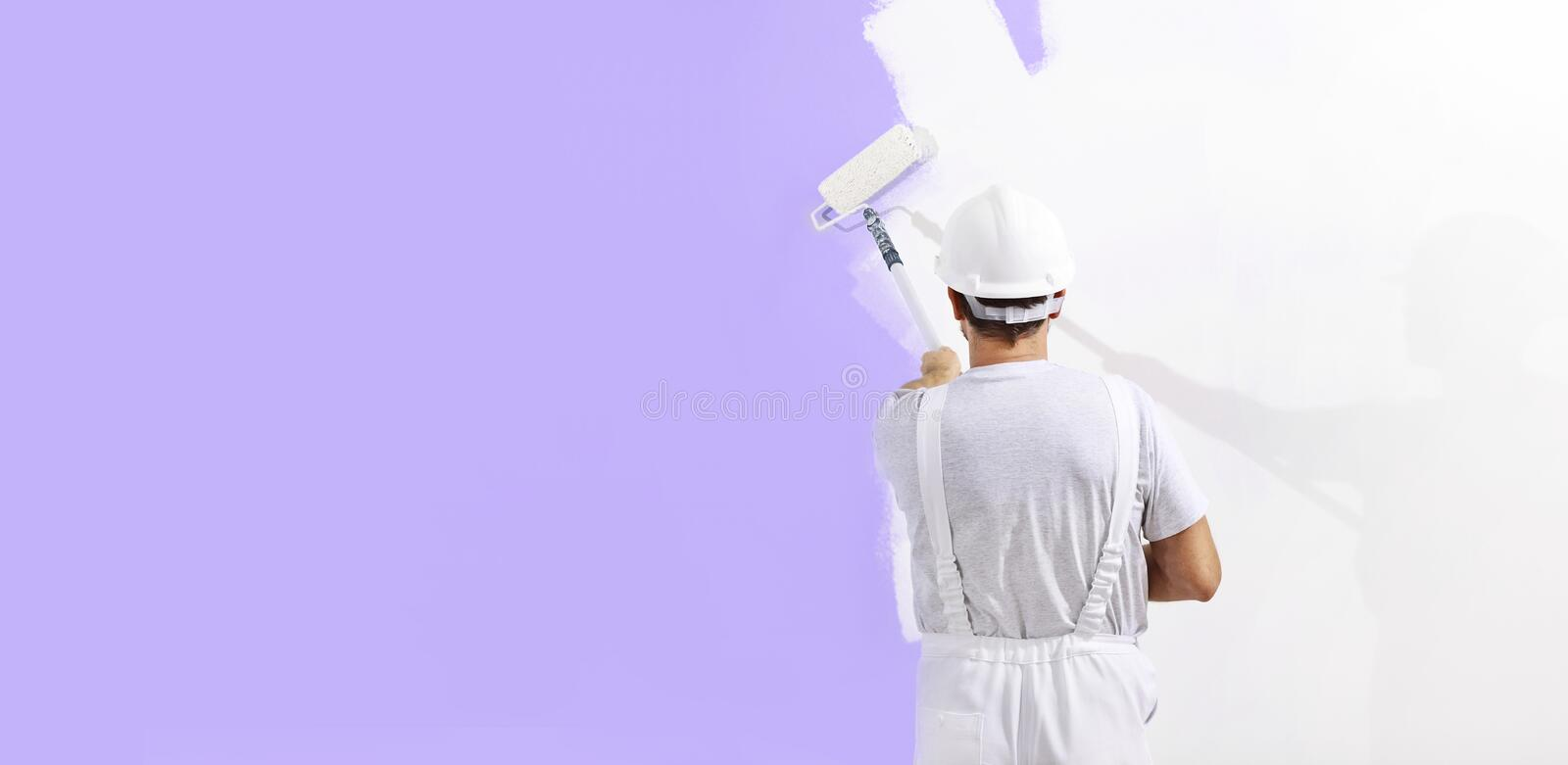Painter man at work with a paint roller, wall painting concept, web banner and copy space template stock photography