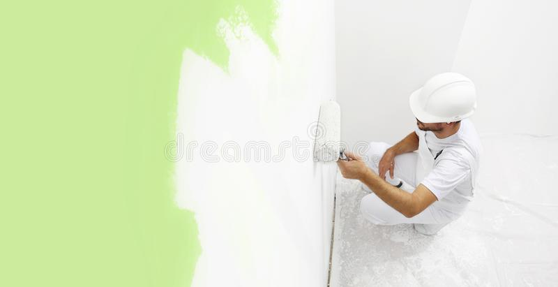Painter man at work with a paint roller, wall painting green col. Or ecological concept, web banner template stock image