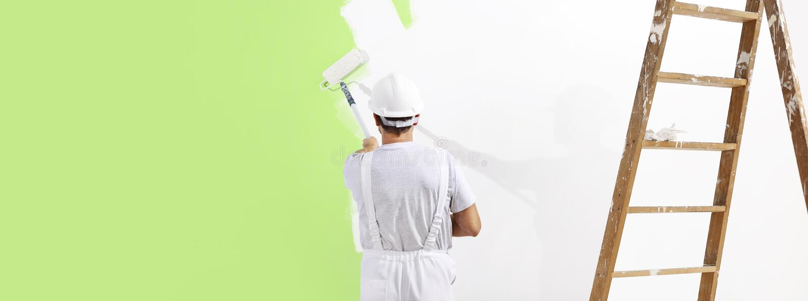 Painter man at work with a paint roller, wall painting green col. Or ecological concept, web banner template royalty free stock photos