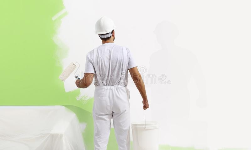 Painter man at work with a paint roller, wall painting green col. Or ecological concept, web banner template royalty free stock photo